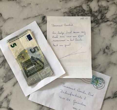 Tevreden bezoeker geeft cadeautje aan Caribabad personeel